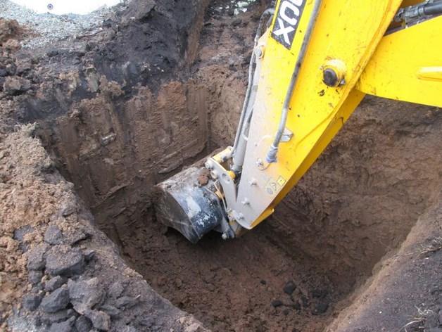 Экскаватор копает яму под колодец
